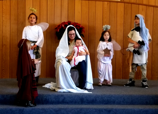 Singing angels, a shepherd, and a wise one gather around the mother and child.