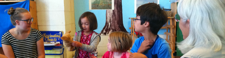 Children and adults play a singing game with a puppet during Sunday School at Berkeley Friends Church
